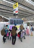 Los pasajeros del aire miran el calendario de salidas en el internat de Bangkok Foto de archivo libre de regalías