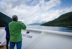 Los pasajeros del barco de cruceros miran hacia fuera para la vida marina Fotografía de archivo libre de regalías
