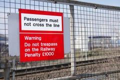 Los pasajeros del ferrocarril no deben cruzar la señal de peligro del peligro del tren no violan ley fina de la pena Fotos de archivo