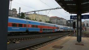 Los pasajeros esperan y conseguir en el tren en el ferrocarril principal de Praga metrajes