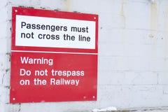Los pasajeros no deben cruzar la línea en la muestra del aviso de la seguridad del ferrocarril Fotografía de archivo