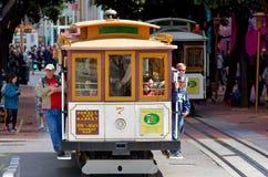 Los pasajeros que montan en Powell-Hyde alinean el teleférico en San Francisco Imagenes de archivo