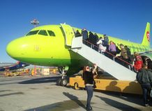 Los pasajeros suben la escalera al avión de las líneas aéreas siberianas S7 imágenes de archivo libres de regalías
