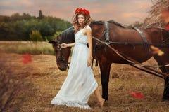 Los paseos de la muchacha en el campo con un caballo caen Fotografía de archivo