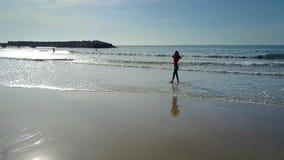 Los paseos de la mujer en la playa mojada de la arena del océano corrigen el pelo