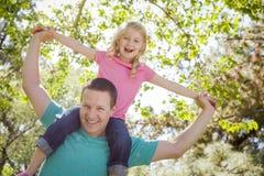 Los paseos lindos de la chica joven llevan a cuestas en sus hombros de los papás fotografía de archivo libre de regalías