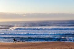 El caminar de la persona que practica surf de la playa de las olas oceánicas Fotos de archivo