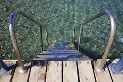 Los pasos con los carriles del hierro descienden en el agua azul clara Fotografía de archivo