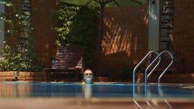 Los pasos delgados de la mujer en la piscina que sostiene las barandillas nadan