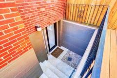 Los pasos exteriores llevan al sótano subterráneo de la casa del ladrillo Foto de archivo libre de regalías