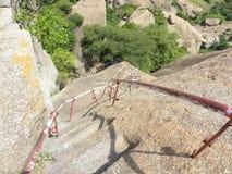 Los pasos a ir abajo de la colina con hierro apoyan mientras que emigran Foto de archivo libre de regalías