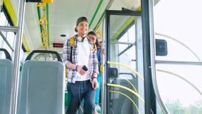 Los passngers felices jovenes de los pares disfrutan de un viaje del transporte público mientras que caminan en una tranvía moder almacen de video