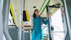 Los passngers felices jovenes de los pares disfrutan de un viaje del transporte público mientras que caminan en una tranvía moder almacen de metraje de vídeo