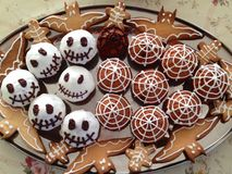 Los pasteles tradicionales a Halloween bajo la forma de magdalenas con un web de araña de una galleta del zombi golpean Imagen de archivo libre de regalías