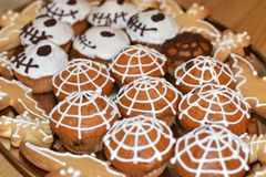 Los pasteles tradicionales a Halloween bajo la forma de magdalenas con un web de araña de una galleta del zombi golpean Imagenes de archivo
