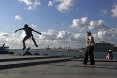 Los patinadores saltan Imagen de archivo