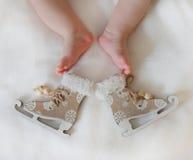 Los patines y las piernas de un recién nacido Imagen de archivo libre de regalías
