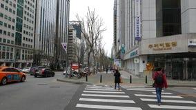 Los peatones cruzan el camino en el paso de peatones en la calle muy transitada, Seul almacen de video