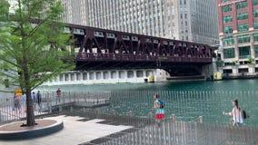 Los peatones cruzan el riverwalk mientras que el tren del EL pasa gastos indirectos en el río Chicago durante la tarde del verano metrajes