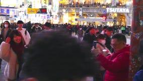 Los peatones cruzan en la travesía de Shibuya por la tarde metrajes