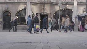 Los peatones cruzan la calle ocupada de la ciudad en Munich, Alemania En el d3ia en invierno frío, cámara inmóvil 60 fps metrajes