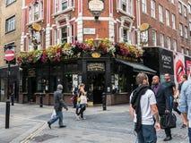 Los peatones dan un paseo más allá del pub blanco del león en Londres Foto de archivo libre de regalías