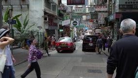 los peatones 4K caminan a través de la calle que hace compras típica y ocupada en Hong Kong almacen de video