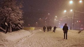 Los peatones se apresuran a lo largo de la acera bajo nevadas anormales por la tarde almacen de metraje de vídeo