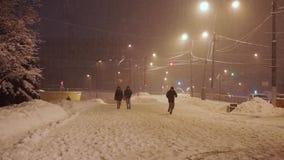 Los peatones se apresuran a lo largo de la acera bajo nevadas anormales por la tarde metrajes