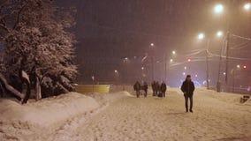 Los peatones se apresuran a lo largo de la acera bajo nevadas anormales por la tarde, cámara lenta almacen de metraje de vídeo
