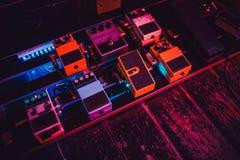 Los pedales de la guitarra pisan fuerte azul amarillo rojo de las cajas imágenes de archivo libres de regalías