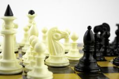 Los pedazos de ajedrez blancos se colocan en un tablero de ajedrez durante un juego del ajedrez, foco en el centro del tablero fotografía de archivo libre de regalías