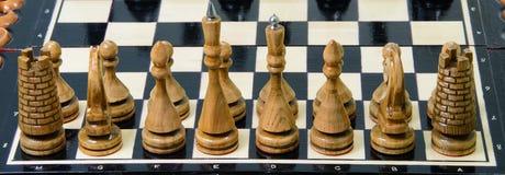 Los pedazos de ajedrez se ponen en el tablero de ajedrez Imagen de archivo libre de regalías