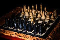 Los pedazos de ajedrez se ponen en el tablero de ajedrez Foto de archivo