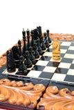 Los pedazos de ajedrez se ponen en el tablero de ajedrez Fotografía de archivo libre de regalías