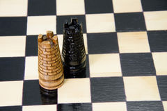 Los pedazos de ajedrez se ponen en el tablero de ajedrez Fotos de archivo