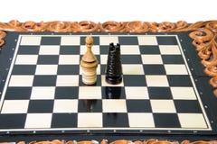 Los pedazos de ajedrez se ponen en el tablero de ajedrez Imagenes de archivo