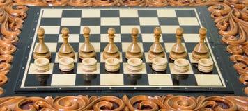 Los pedazos de ajedrez se ponen en el tablero de ajedrez Imágenes de archivo libres de regalías