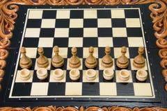 Los pedazos de ajedrez se ponen en el tablero de ajedrez Foto de archivo libre de regalías