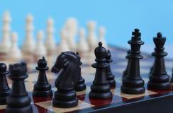 Los pedazos de ajedrez se ponen en un tablero a cuadros para comenzar un juego fotografía de archivo