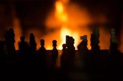 Los pedazos de ajedrez siluetean retroiluminado por la chimenea foto de archivo