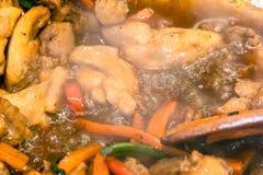 Los pedazos de carne del pollo se hierven con las verduras imagen de archivo
