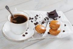 Los pedazos de chocolate con una taza de café presentaron en un na blanco Fotografía de archivo libre de regalías