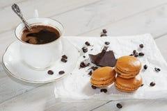 Los pedazos de chocolate con una taza de café presentaron en un na blanco Foto de archivo