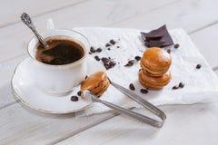 Los pedazos de chocolate con una taza de café presentaron en un na blanco Fotos de archivo libres de regalías
