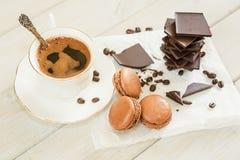 Los pedazos de chocolate con una taza de café presentaron en un na blanco Imágenes de archivo libres de regalías