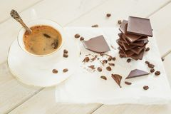 Los pedazos de chocolate con una taza de café presentaron en un na blanco Imagenes de archivo