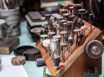 Los pedazos de Dremel fijaron en el lugar de trabajo del ` s del joyero Fotografía de archivo libre de regalías