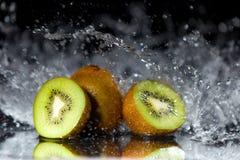 Los pedazos de kiwi con agua salpican y reflexión en un CCB negro Fotos de archivo libres de regalías