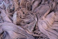 Los pedazos de la tela, la ropa vieja y las materias textiles se cortan en las tiras que esperan reciclan imagen de archivo